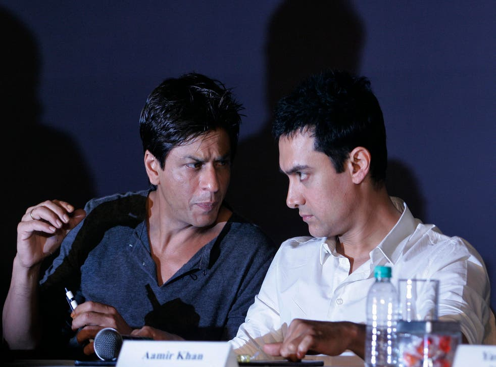 In this April 7, 2009, file photo, Bollywood actors Shah Rukh Khan, left, and Aamir Khan speak during a press conference in Mumbai
