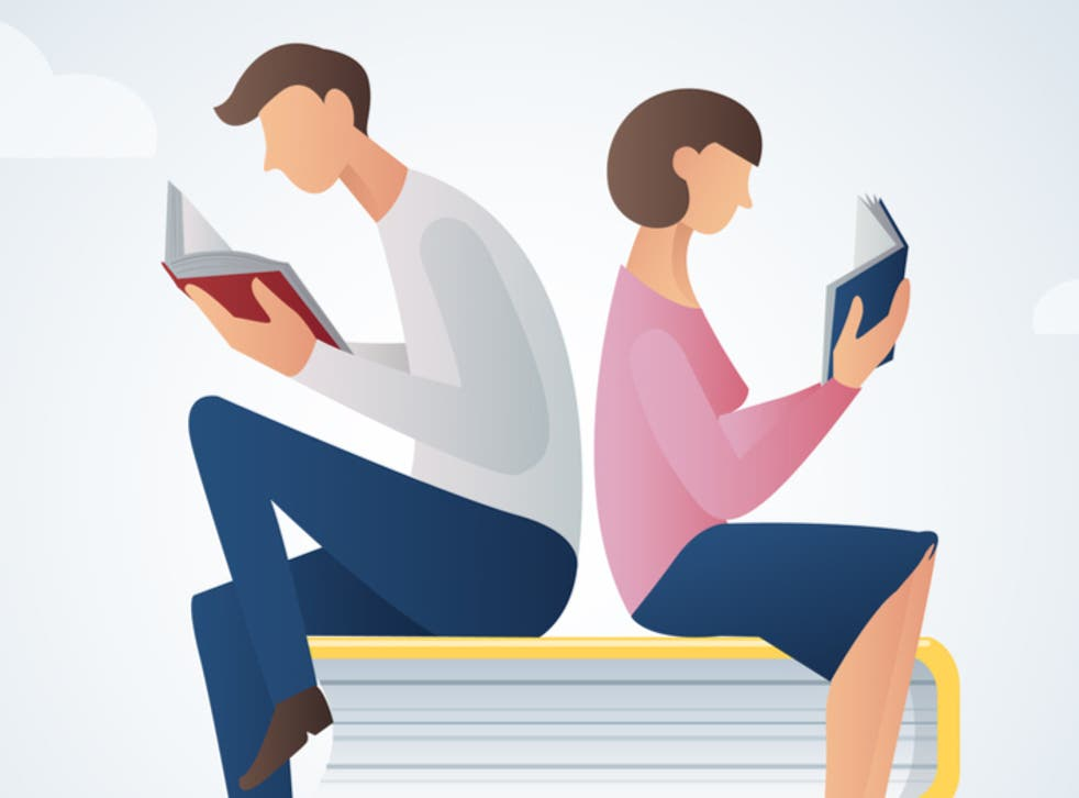 man and woman reading books sitting on many books