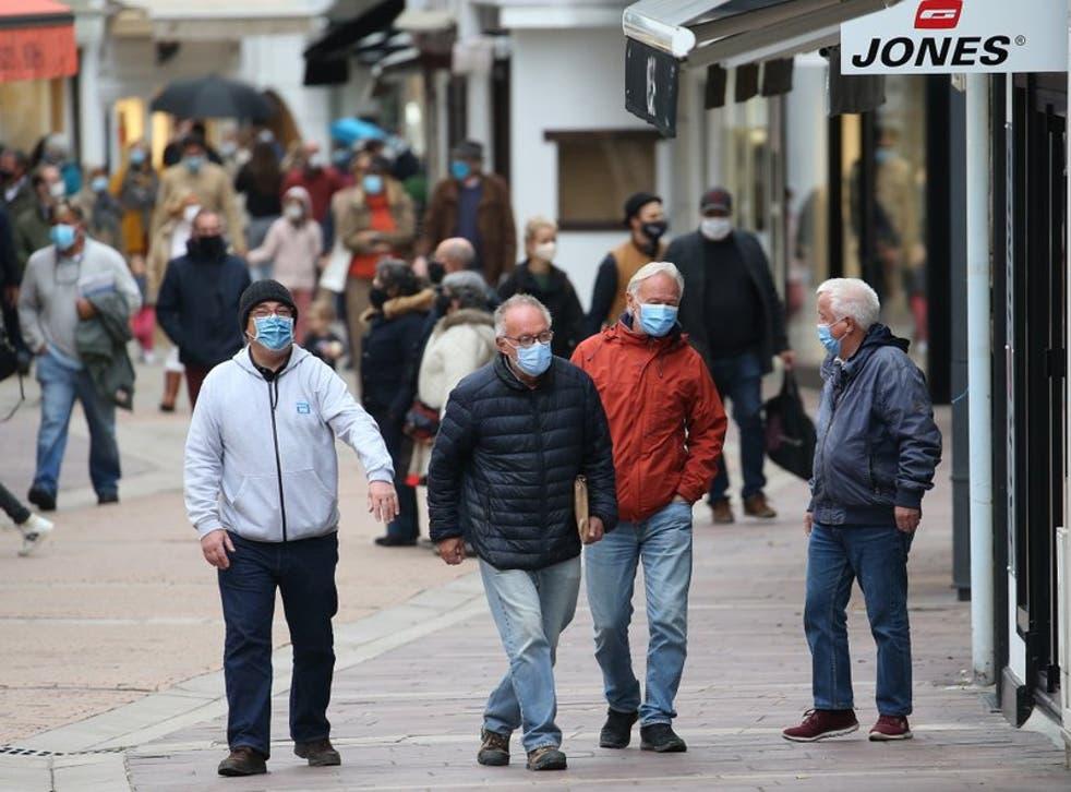 Personas con máscaras debido al coronavirus caminan por una calle en Saint Jean de Luz, Francia.