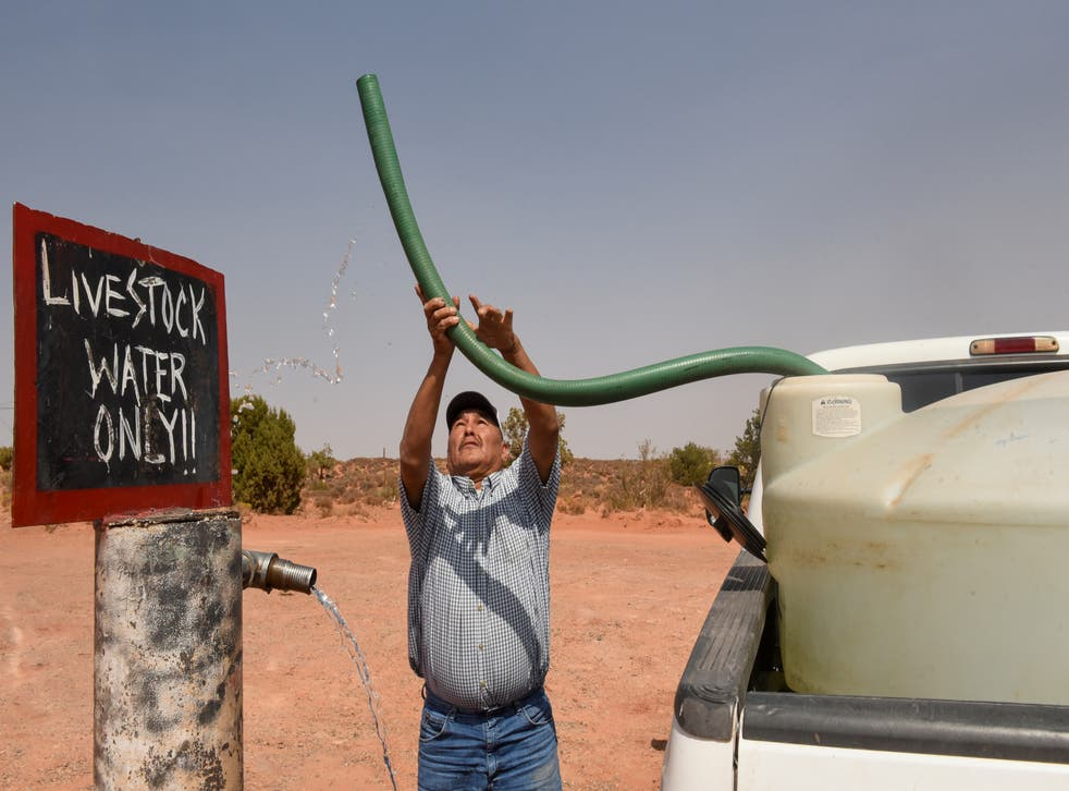 <p>Eugene Boonie, 55, of the Navajo Nation fills up his water tank at a livestock spigot</p>