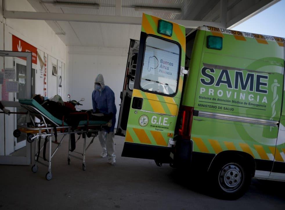 Trabajadores de la salud llevan a un paciente en camilla a un hospital para enfermos de COVID-19 en Mar del Plata, Argentina.
