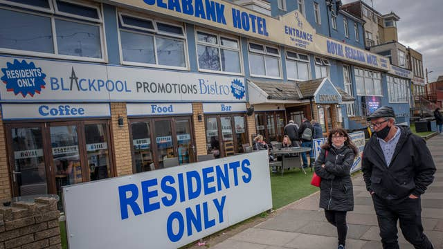 Pedestrians walk pas the Royal Seabank Hotel in Blackpool as Lancashire enters tier 3 of the government's coronavirus alert system