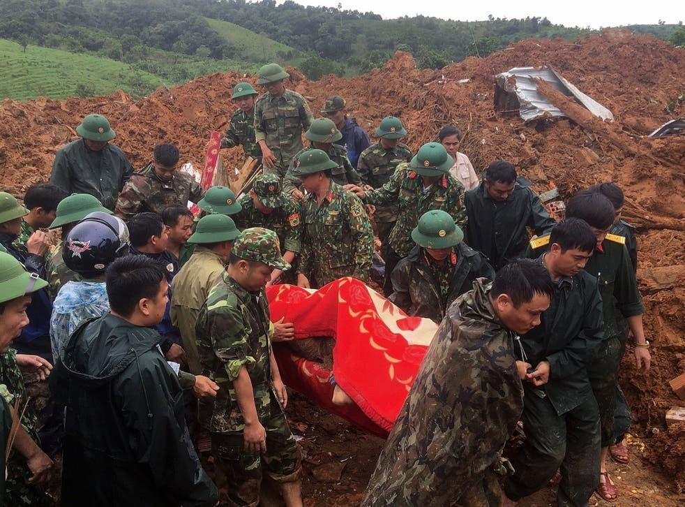 Personal militar portando un cuerpo recuperado del lugar de un deslizamiento de tierra en la provincia de Quang Tri, en el centro de Vietnam.
