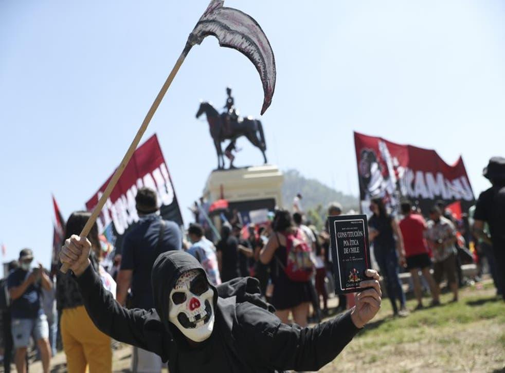 Un manifestante con una máscara sostiene la constitución de Chile mientras se manifiesta durante el primer aniversario del inicio de las protestas masivas contra el gobierno desencadenadas por el aumento de la tarifa del metro, que llevó a demandas por un cambio social en todo el país en Santiago de Chile, el domingo 18 de octubre del 2020. (Foto AP/Esteban Félix)