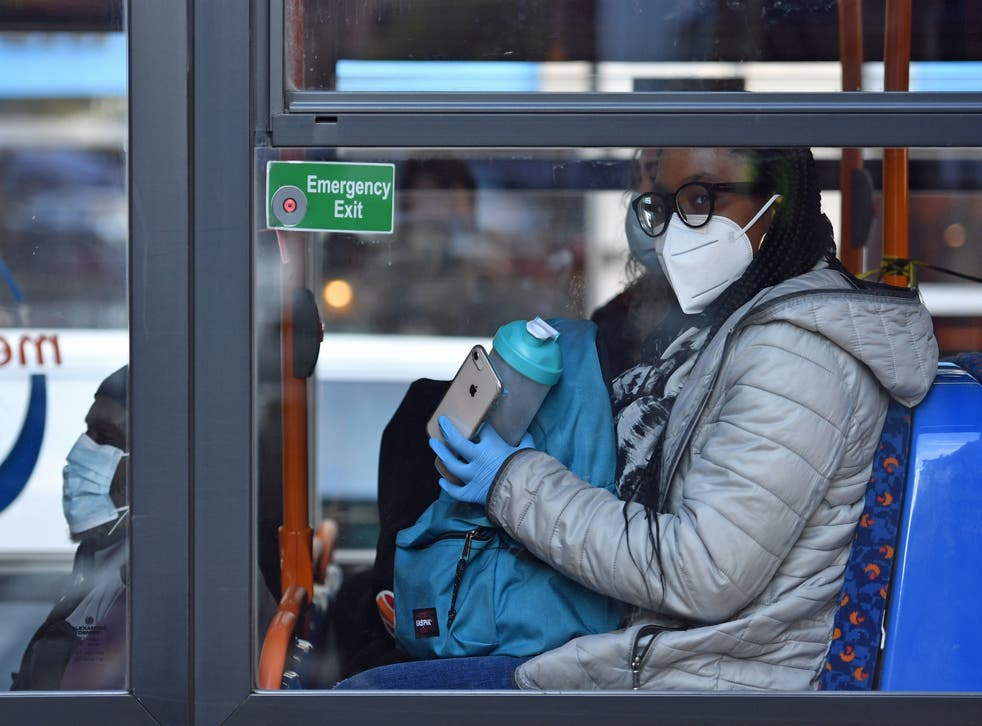 A person wearing a mask and gloves on a bus on Oxford Road in Manchester