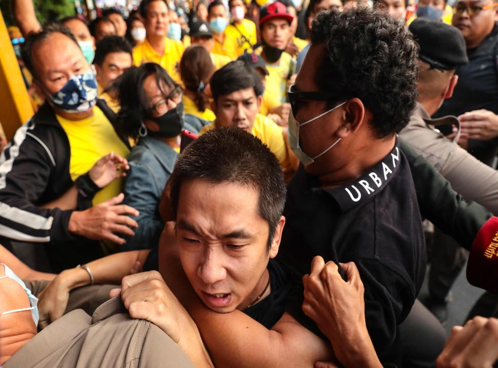 A man is held back during scuffles between royalist supporters and pro-democracy protesters at Ramkhamhaeng University in Bangkok on Wednesday