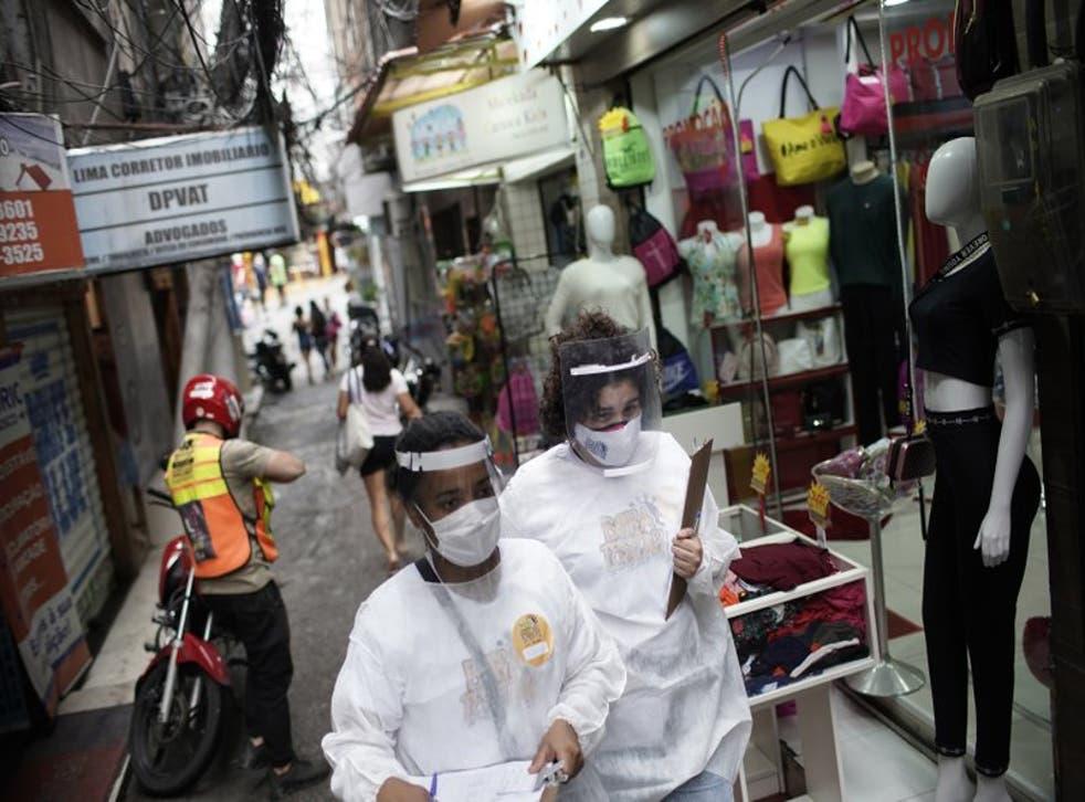 Personal de salud recorre la favela de Rocinha para realizar pruebas de coronavirus a la población como parte de una campaña de pruebas rápidas de una organización civil en Río de Janeiro, Brasil, el jueves 8 de octubre de 2020. (AP Foto/Silvia Izquierdo)