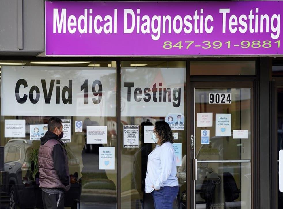 Una empleada de Exam Corp Lab habla con un paciente formado para realizarse una prueba de COVID-19 en Niles, Illinois, el miércoles 21 de octubre de 2020. (Foto/Nam Y. Huh)