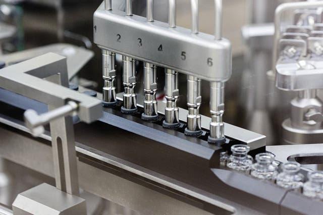 En esta imagen de marzo de 2020, cortesía de Gilead Sciences, se observa el proceso de aplicación de tapones de goma en las dosis del fármaco en desarrollo remdesivir, en la fábrica de Gilead en Estados Unidos. (Gilead Sciences via AP)
