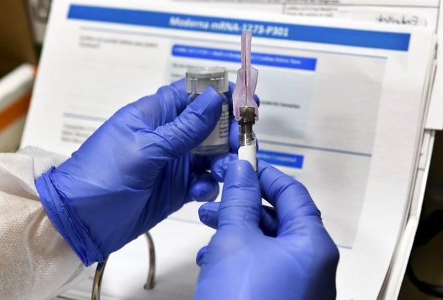 Enfermera prepara una inyección que es parte de una posible vacuna contra el COVID-19.