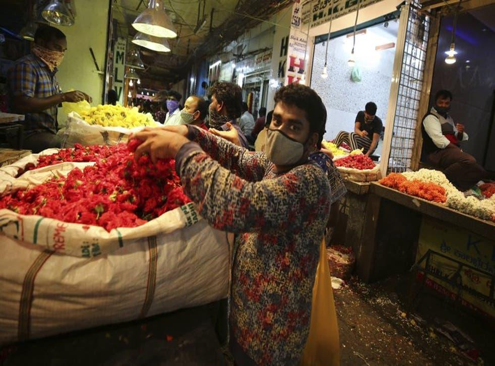 Vendedores colocan flores en un mercado al por mayor antes del festival hindú del Dussehra, en Bengaluru, India.