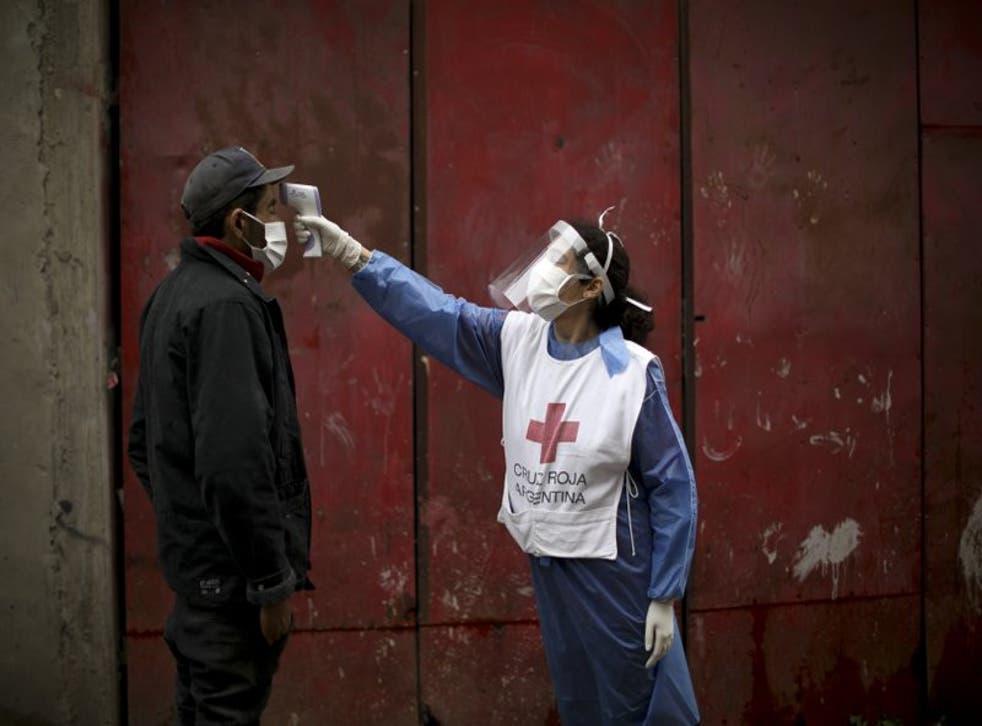 En esta imagen del 6 de junio de 2020, una voluntaria de la Cruz Roja le toma la temperatura a un hombre en el barrio de Fraga durante el cierre ordenado por el gobierno para frenar la propagación del nuevo coronavirus en Buenos Aires. (Foto/Natacha Pisarenko, Archivo)