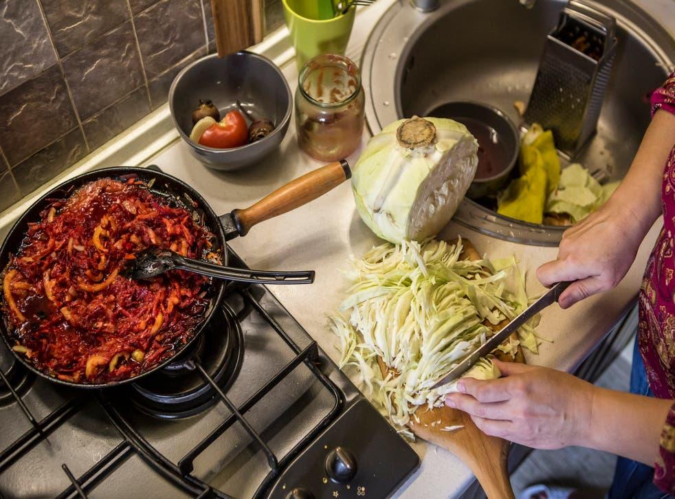 Oksana Chadaieva, 50, chops a cabbage in her kitchen as she prepares borscht