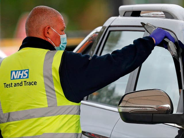 <p>A driver receives a Covid-19 self-test kit from an NHS Test and Trace worker in Chessington</p>