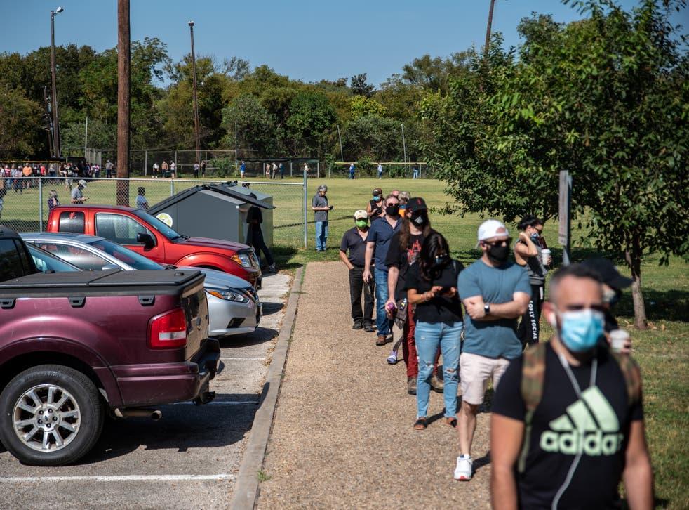 Los primeros votantes esperan en fila en un lugar de votación el 13 de octubre en Austin, Texas.