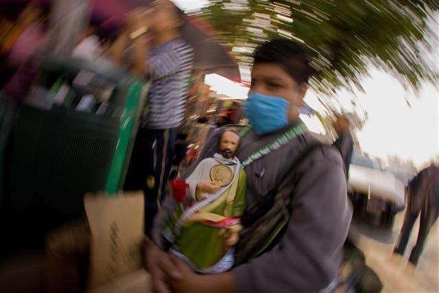 Un hombre sostiene una imagen de San Judas Tadeo, santo patrono de las causas imposibles, en Ciudad de México.