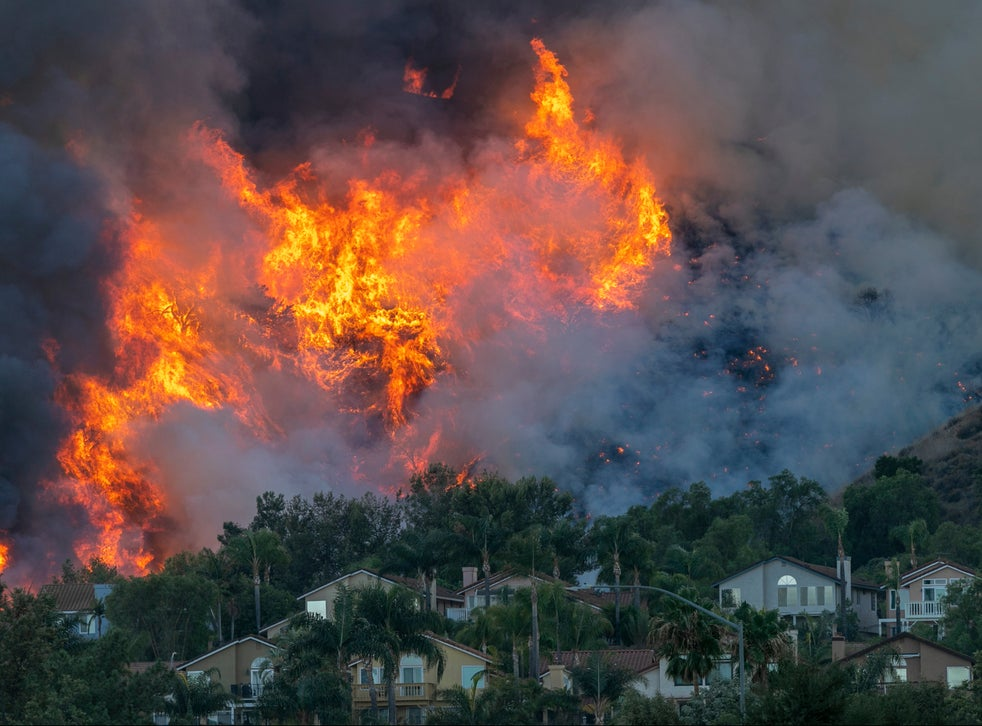Flames rise near homes during the Blue Ridge wildfire on October 27, 2020 in Chino Hills, California. A new poll has found that the majority of Americans think we are running out of time to save the planet from the climate crisis