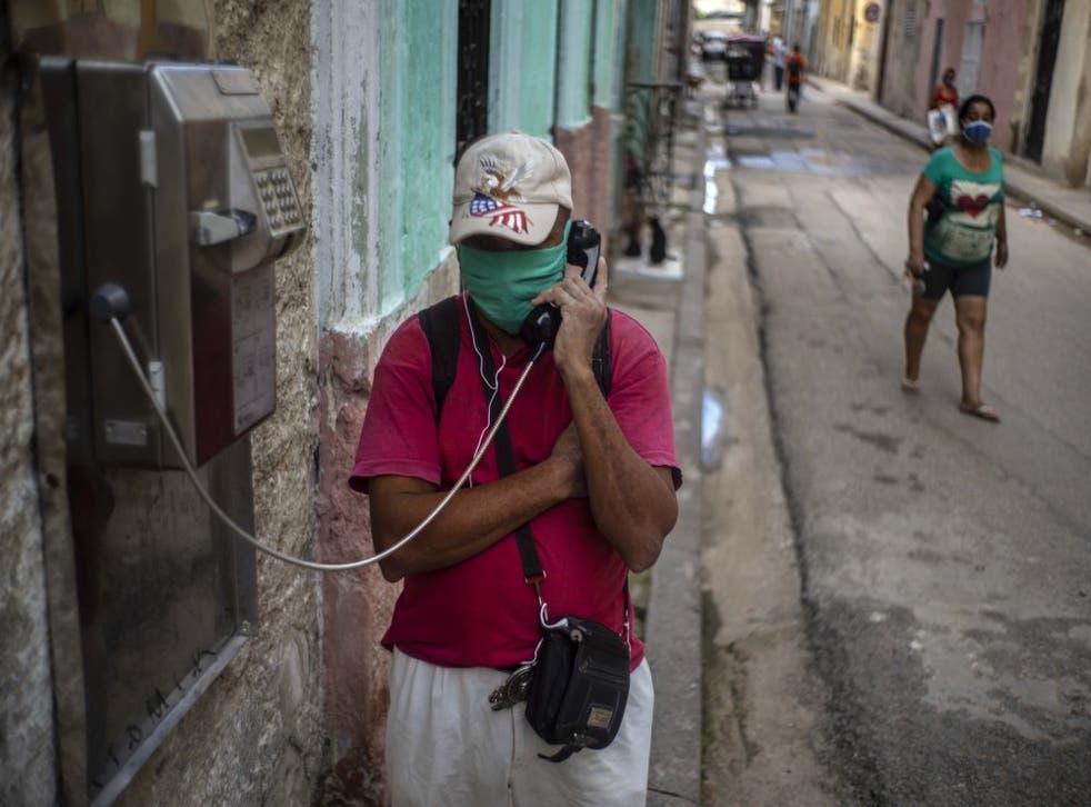 Con una mascarilla protectora en medio de la pandemia del nuevo coronavirus, un hombre habla por un teléfono público en La Habana Vieja, Cuba, el lunes 26 de octubre de 2020. (Foto/Ramón Espinosa)