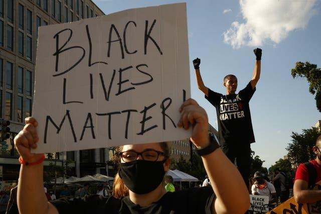 Manifestantes protestan frente a una hilera de policías en Washington.