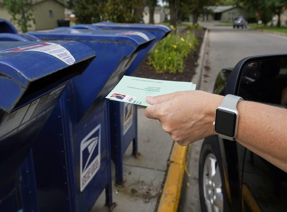 En esta fotografía de archivo del 18 de agosto de 2020, una persona deposita en un buzón una solicitud para que le envíen por correo las papeletas electorales en Omaha, Nebraska. (Foto/Nati Harnik, Archivo)
