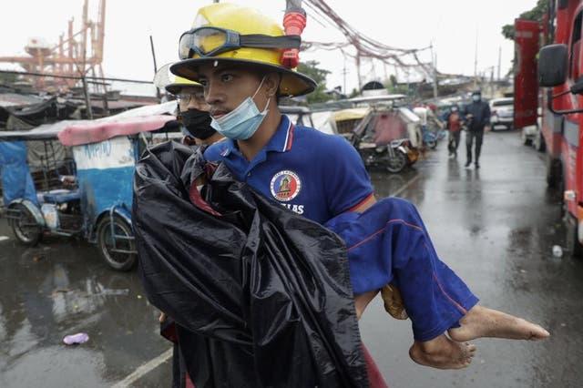 Un rescatista lleva en brazos a un niño enfermo durante la evacuación de una población costera en Manila, Filipinas, el domingo 1 de noviembre de 2020. Un súpertifón arremetió contra el este de Filipinas. En torno a un millón de personas fueron evacuadas. (Foto/Aaron Favila)