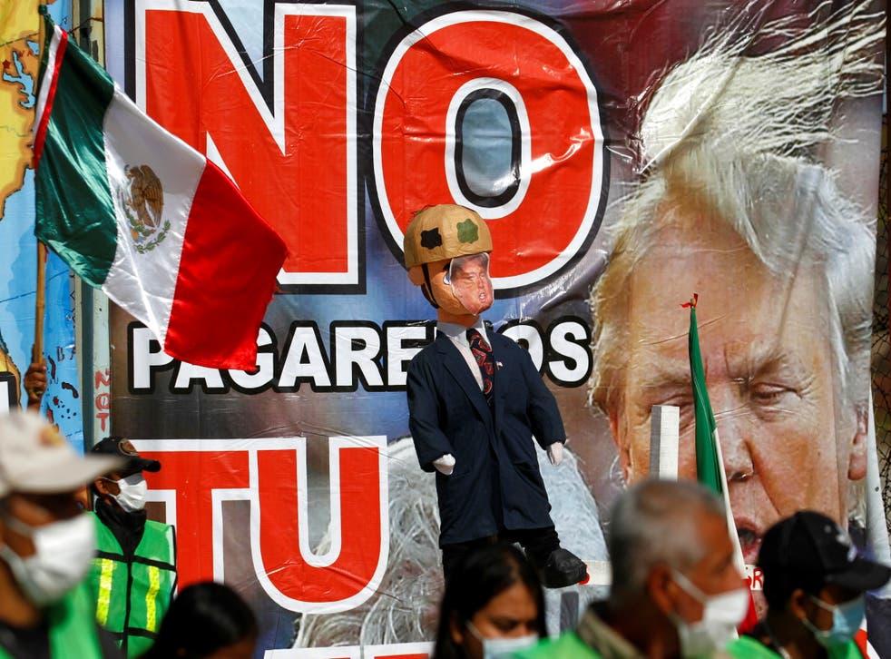 <p>Migrantes sostienen una piñata con la imagen del presidente de los Estados Unidos, Donald Trump.</p>