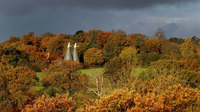 An oast house surrounded by autumn colours in the morning sunshine near Hawkhurst in Kent