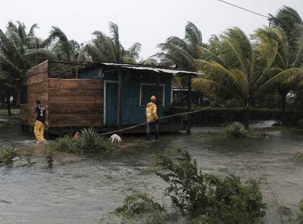 Dos hombres caminan por los perímetros de una casa rodeados por las inundaciones provocadas por el huracán Eta en Wawa.