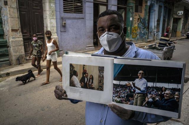 """<p>En esta foto de archivo del 22 de octubre de 2020 con una máscara facial en medio de la nueva pandemia de coronavirus, Cristóbal Márquez, dueño de """"Cristobal's"""", el restaurante donde Michelle y Barak Obama almorzaron durante su visita a Cuba en 2016, muestra el libro realizado por el fotógrafo de la Casa Blanca Pete Souza, en La Habana, Cuba.</p>"""