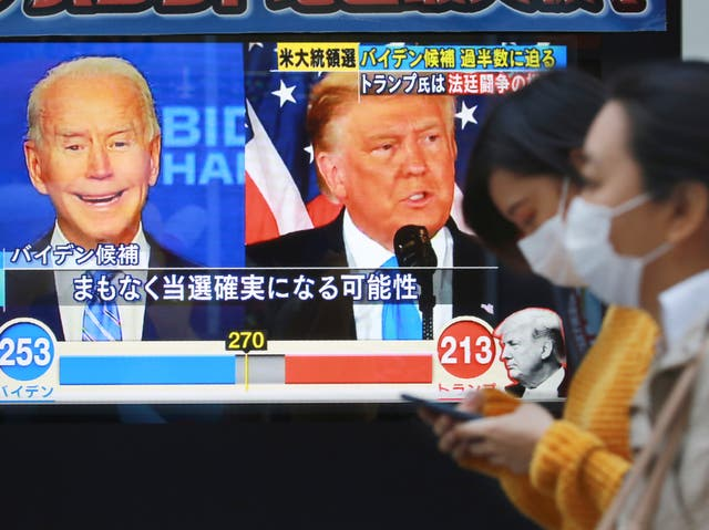 <p>City goers pass a TV screen reporting on the US election in Tokyo</p>