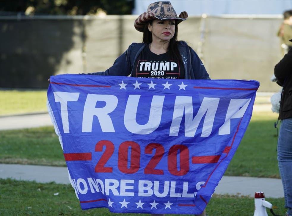 Una partidaria de la reelección de Donald Trump como presidente de Estados Unidos sostiene una bandera, amnifestándose en el norte del Bulevar de Santa Mónica, en Beverly Hills, California...