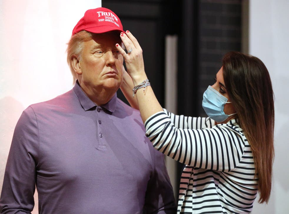 <p>A member of the Madame Tussauds studios team adjusts a wax figure of Donald Trump which has been re-dressed in golf wear following the 2020 US presidential election</p>