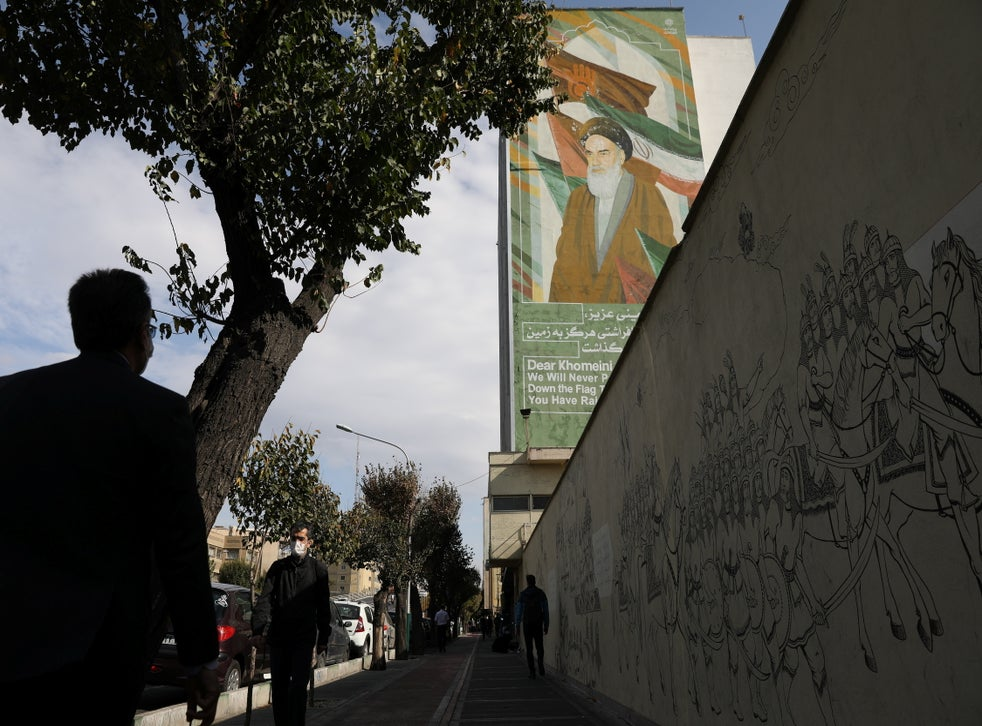 People walk on a pavement as a banner depicting Iran's late leader Ayatollah Ruhollah Khomeini. Majid Asgaripour/WANA (West Asia News Agency) via REUTERS ATTENTION EDITORS