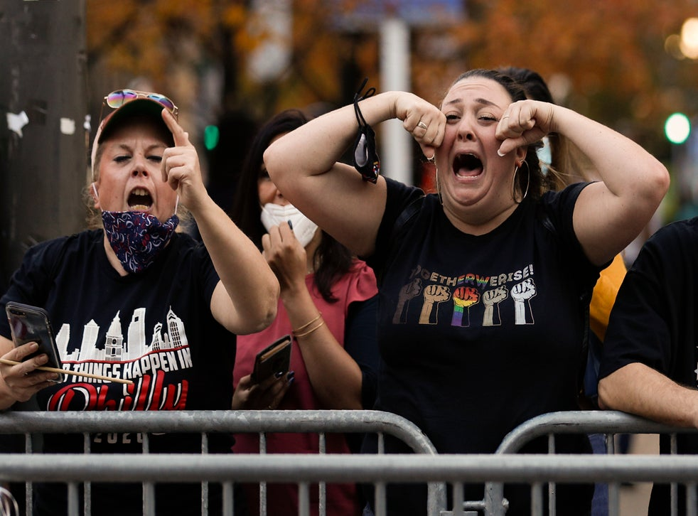 Joe Biden fans taunt Trump supporters in Washington, but the outgoing president could make moves which appeal to his base before he leaves office (AP Photo/Rebecca Blackwell)