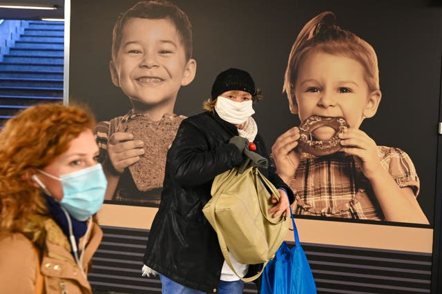 Commuters wear face masks as they walk through an underpass in Budapest on November 10, 2020, hours before as a partial lockdown comes into force
