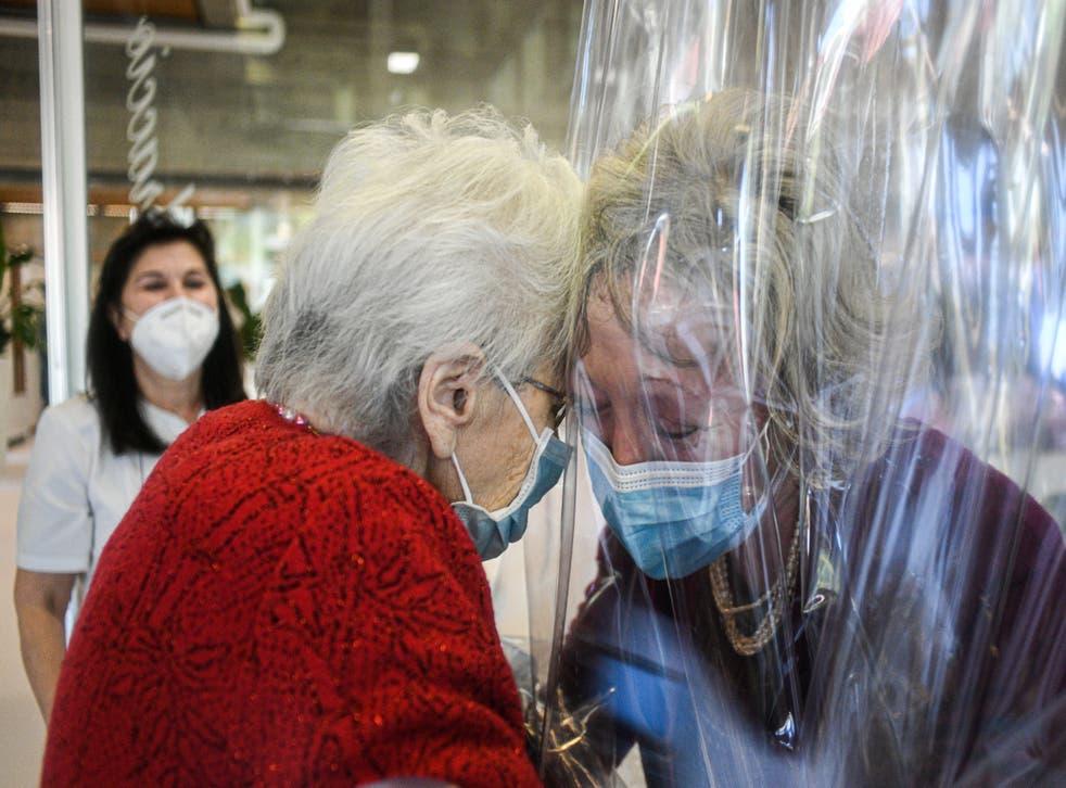 A resident (left) of the Domenico Sartor nursing home in Castelfranco Veneto, near Venice, hugs her visiting daughter