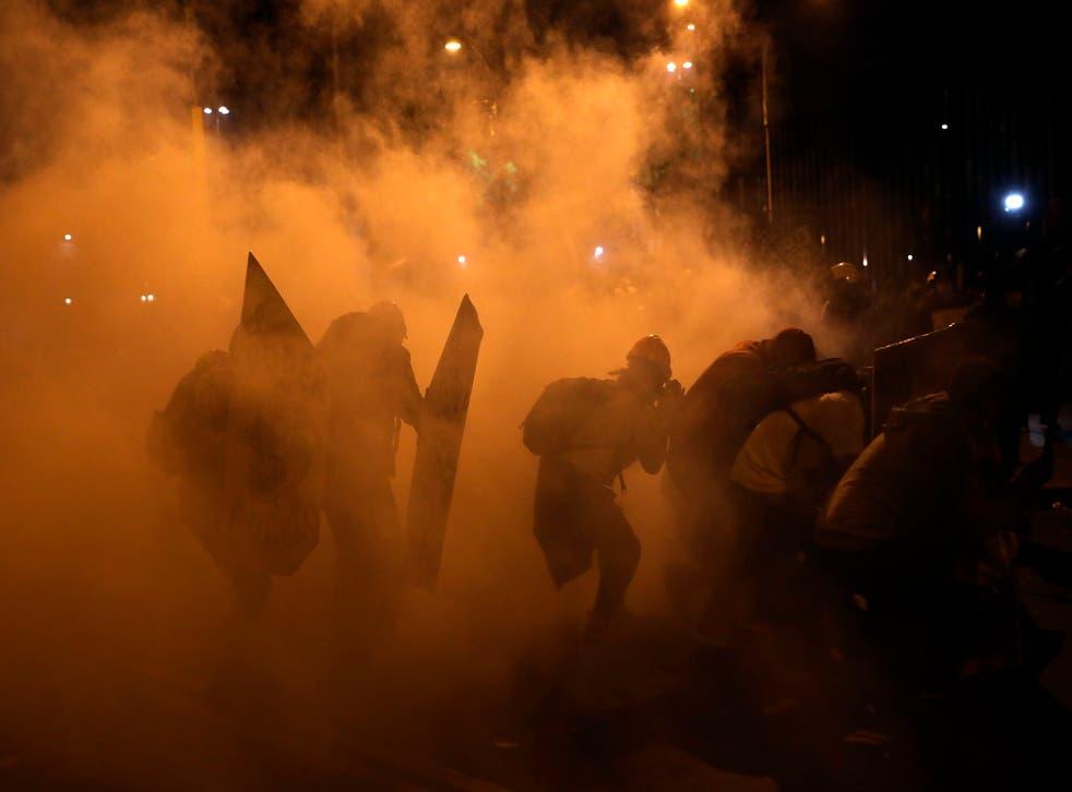 <p>Manifestantes buscan resguardo del gas lacrimógeno lanzado por la policía para dispersar a los manifestantes reunidos en la Plaza San Martín en repudio del nuevo gobierno del presidente Manuel Merino, en Lima, el sábado 14 de noviembre de 2020.</p>