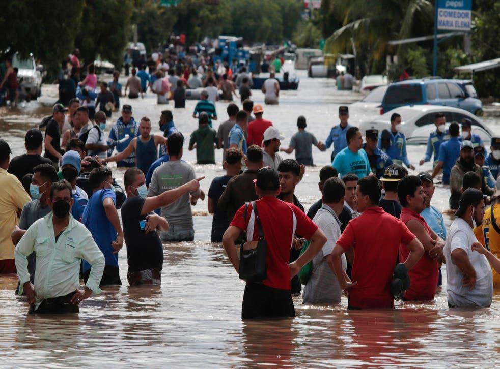 <p>Múltiples personas vadean un camino inundado el jueves 5 de noviembre de 2020 tras el paso del huracán Eta, en Planeta, Honduras.</p>