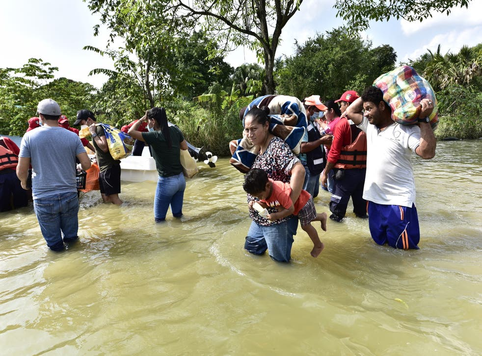 <p>Inhabitants walk through an avenue flooded by heavy rains in Macuspana, Mexico (EPA/Jaime Avalos)</p>