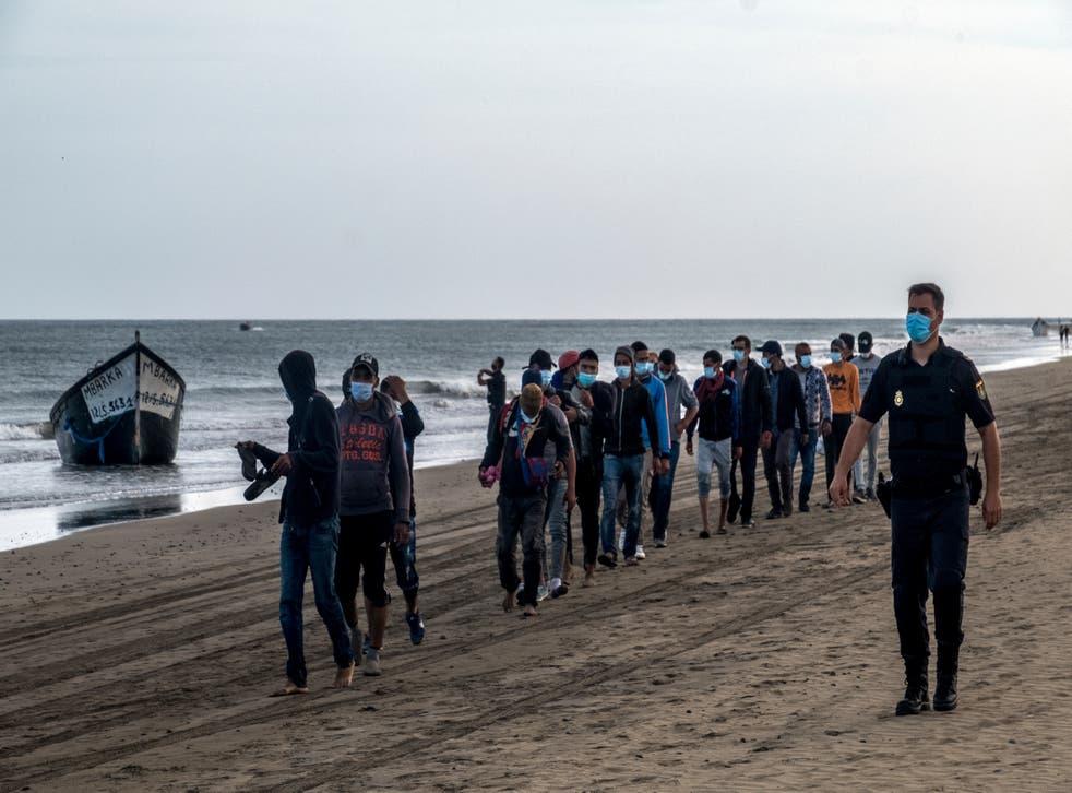 <p>En esta foto del 20 de octubre del 2020, migrantes de Marruecos caminan por la costa acompañados por la policía española tras llegar a la isla de Gran Canaria. El gobierno de España trata apresuradamente de lidiar con el consistente flujo de migrantes de África occidental a las Islas Canarias, abriendo un segundo campamento temporal, dijeron las autoridades el 18 de noviembre, al tiempo que aumentan las tensiones políticas en el archipiélago Atlántico.</p>