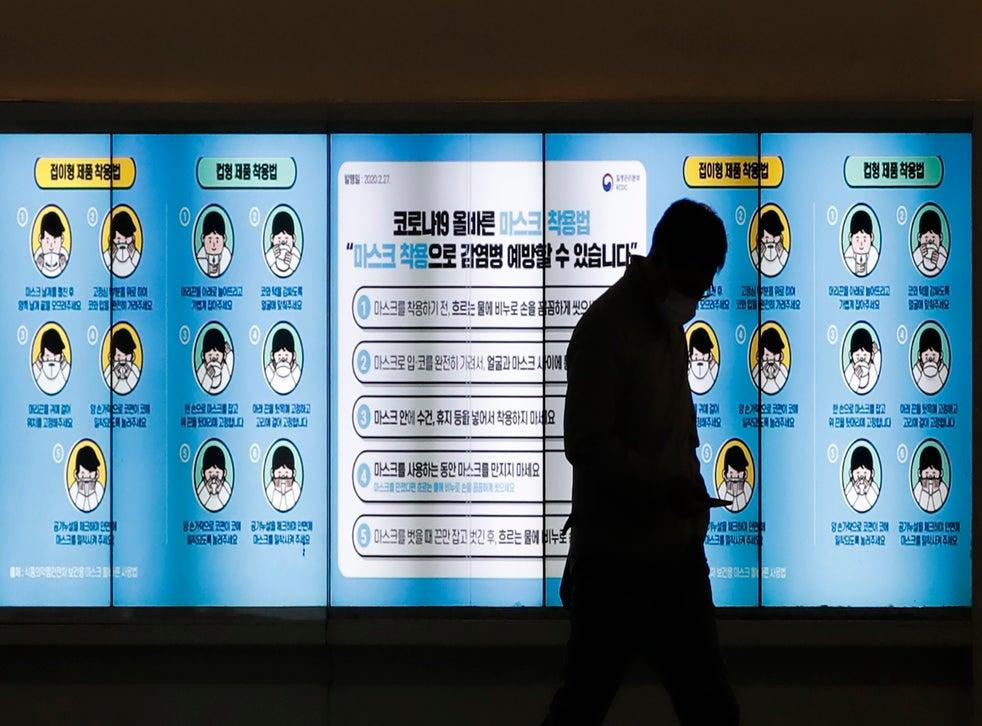 """<p>Un hombre con mascarilla pasa por delante de una pantalla que muestra las medidas de precaución contra el coronavirus, en Seúl, Corea del Sur, el 20 de noviembre de 2020. El letrero dice """"Como llevar mascarilla"""".</p>"""