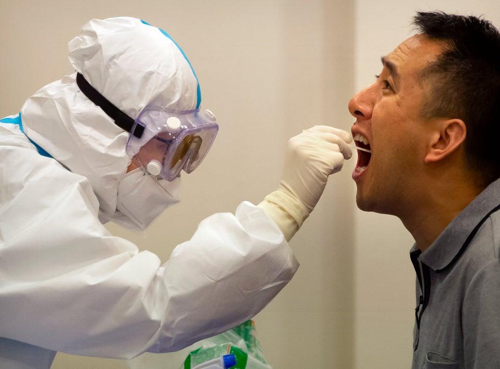 <p>Personal médico le realiza una prueba de coronavirus a un hombre en Hainan, China, el 22 de noviembre de 2020.</p>