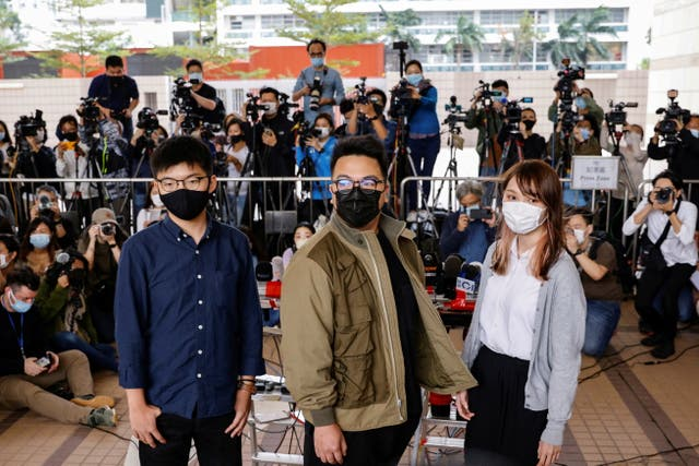 <p>Pro-democracy activists Ivan Lam, Joshua Wong and Agnes Chow arrive at the West Kowloon Magistrates' Courts on Monday (23 November)</p>