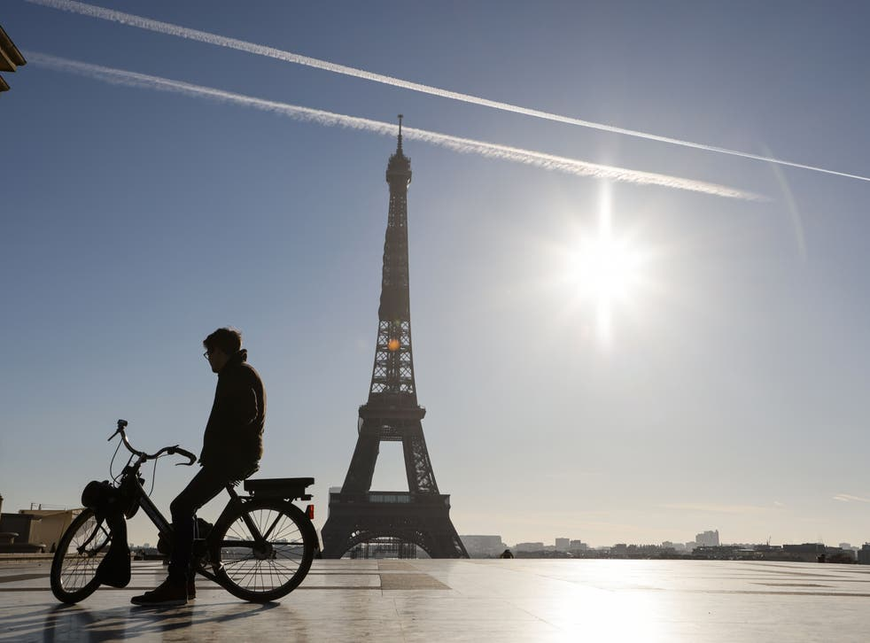 A man rides an electric bike in front of the Eiffel Tower during France's second coronavirus lockdown