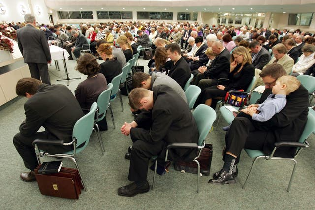 Members of the Jehova's Witnesses Church pray during a religious service