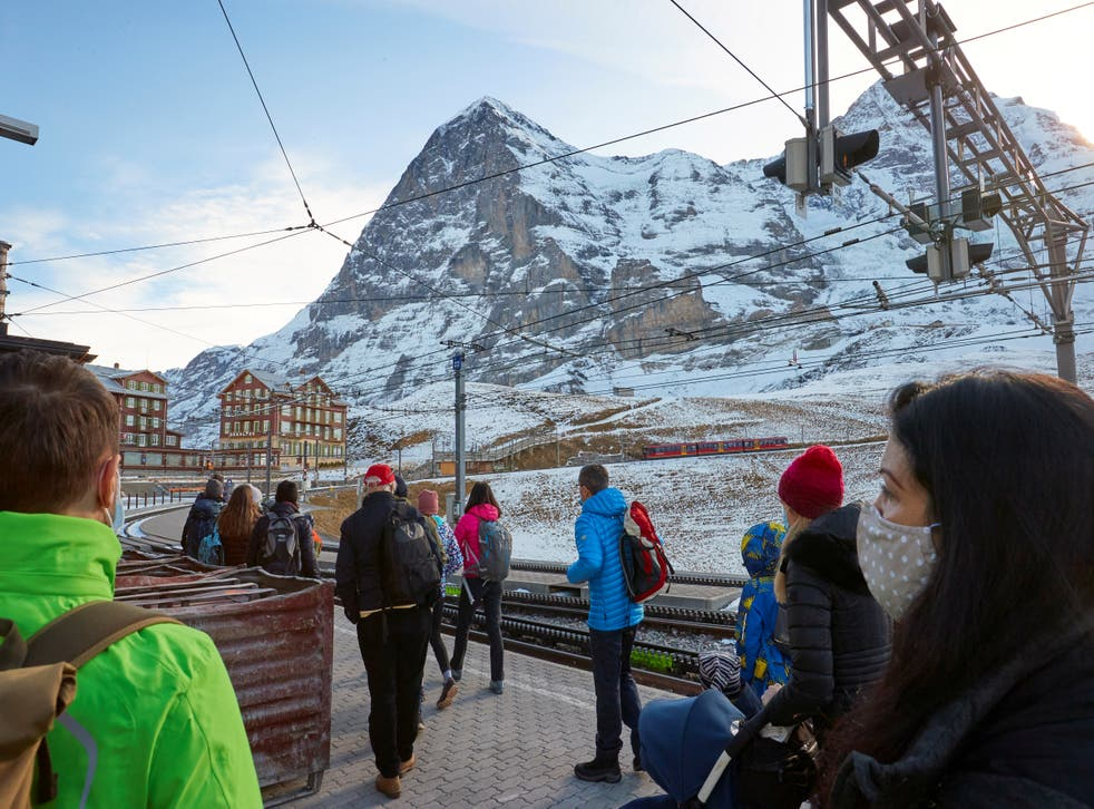 <p>Passengers wearing protective masks wait to board the Jungfraujoch train in the ski resort of Grindelwald, Switzerland</p>