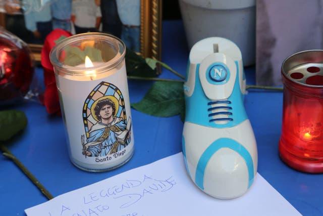 """<p>Una vela que dice """"Santo Diego"""" y un zapato con el logo del club de fútbol SSC Napoli.</p>"""