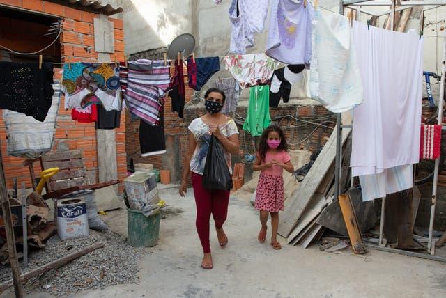 SAO PAULO, BRASIL - 25 DE JUNIO: Nilzete Neves Reis, de 42 años, desempleada, y su sobrina de 7 años, Maria Clara Santos Reis, caminan a casa con la donación de alimentos que recibieron en medio de la pandemia de coronavirus el 25 de junio de 2020 en Sao Paulo, Brasil. El Instituto Baccarelli es una organización sin fines de lucro que enseña música a más de 1200 niños y jóvenes desfavorecidos y socialmente vulnerables en Heliópolis, una de las mayores favelas de Sao Paulo de más de 200. 000 habitantes. El Instituto es responsable de crear la primera orquesta del mundo que surgió en una favela, la Orquesta Sinfónica de Heliópolis. Con el impacto social y económico de la pandemia de coronavirus (COVID-19) en estas comunidades pobres, el Instituto Baccarelli decidió recaudar fondos y las donaciones se utilizan para alimentos, productos de limpieza e higiene.