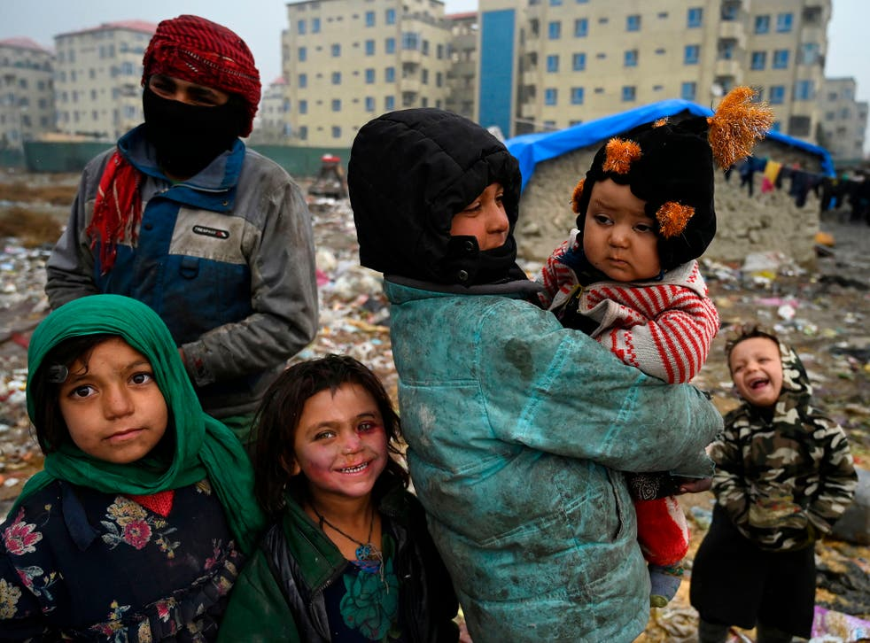 <p>Internally displaced Afghan children stand outside their temporary mud house at a refugee camp in Kabul</p>