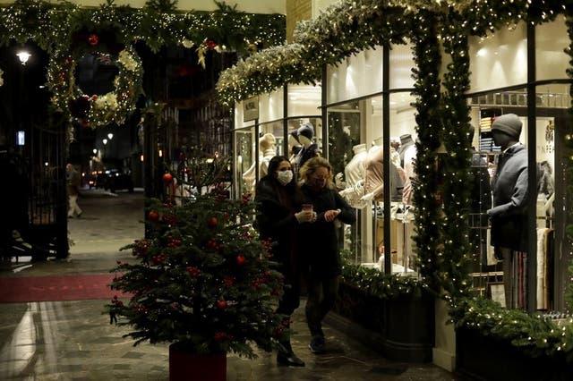 Unas mujeres con cubrebocas por el coronavirus pasan frente a una tienda de ropa en Burlington Arcade, Londres, el 25 de noviembre de 2020.